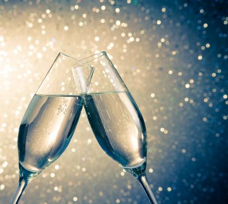 Champagner-Flöten mit goldenen Blasen machen Jubel auf blauem Licht Bokeh Hintergrund mit Platz für Text Standard-Bild - 24813856