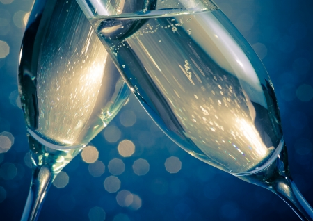 detail of champagne flutes with golden bubbles make cheers on blue light bokeh background with space for text 스톡 콘텐츠