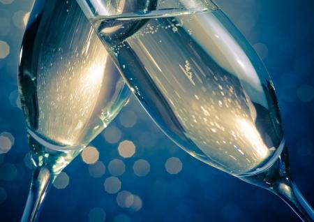 detalj av champagne flöjter med gyllene bubblor gör jubel på blått ljus bokeh bakgrund med utrymme för text