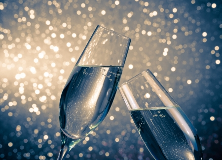 a pair of champagne flutes with golden bubbles make cheers on blue light bokeh background with space for text 스톡 콘텐츠