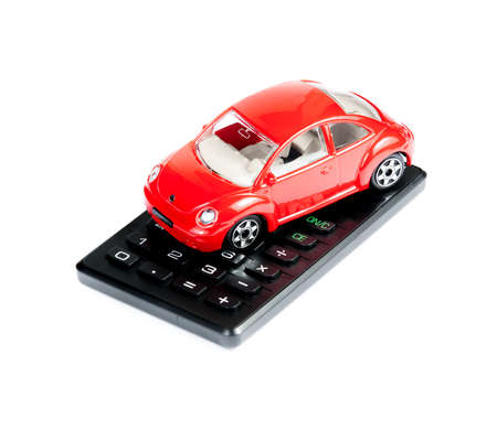 toy car and calculator concept for insurance, buying, renting, fuel or service and repair costs, on white background photo