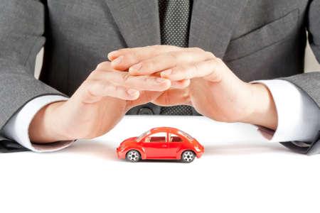 affärsman skydda med händerna en röd bil på vitt bord, koncept för försäkring, köpa, hyra, bränsle eller servicekostnader och reparations Stockfoto