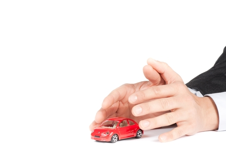 undertaking: businessman protect with his hands a red car on white background, car insurance concept