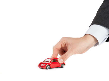 toy car and hand of man, concept for insurance, buying, renting, fuel or service and repair costs, on white background photo