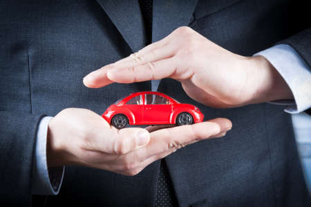 cars parking: businessman protect with his hands a red car on white table, concept for insurance, buying, renting, fuel or service and repair costs Stock Photo