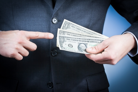 earn money: detail of businessman with dollars in his hand on blue , concept for business and earn money