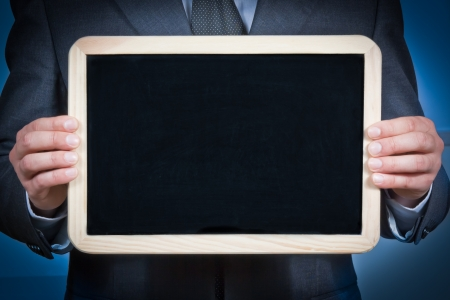 businessman holds a blank blackboard with the hands on a blue