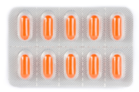 top of view of orange pills packed in blister on white background photo