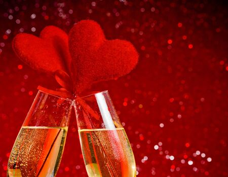 two champagne flutes with golden bubbles and red velvet hearts make cheers on red bokeh background with space for text, concept of valentine day photo