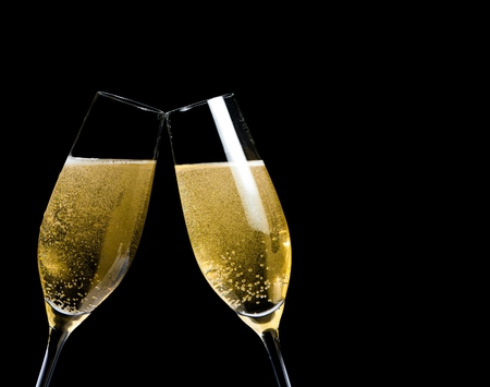 two champagne flutes with golden bubbles make cheers on black background with space for text