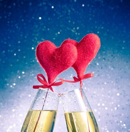 champagne flutes with golden bubbles and red velvet hearts make cheers on blue bokeh background with space for text, concept of valentine day photo