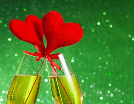two champagne flutes with golden bubbles and red velvet hearts make cheers on green bokeh background with space for text, concept of valentine day photo