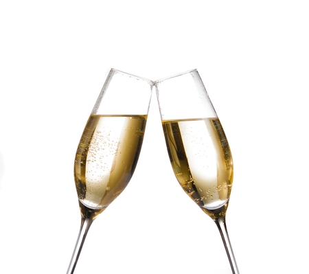 two champagne flutes with golden bubbles make cheers on white background with space for text