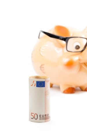 fifty euro banknote in front of unfocused piggy bank with glasses on white background with space for text, concept for business and save money photo