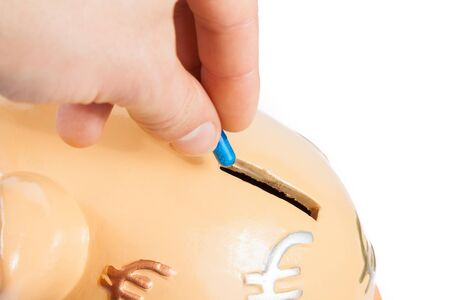 hand inserting a pill into a piggy bank on white background with space for text, concept for save money photo