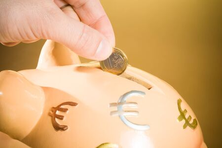 detail of a hand inserting a coin into a piggy bank, concept for business and save money on golden background photo