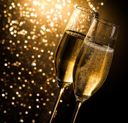 champagne flöjter med gyllene bubblor på mörk gyllene ljus bokeh bakgrund med utrymme för text