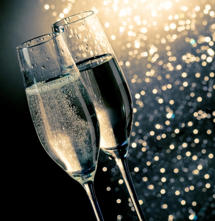 champagne flutes with golden bubbles on dark blue light bokeh background with space for text