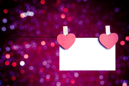 two decorative red hearts with greeting card hanging on blue and violet light bokeh background photo