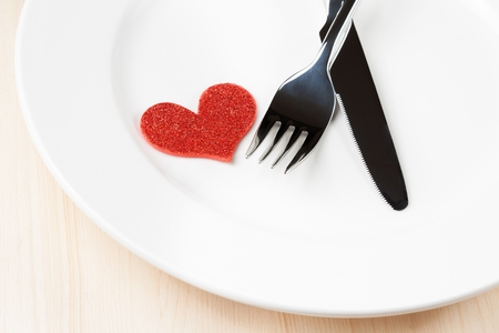 decorative red heart near a fork and knife on flat on wood background, concept valentine day dinner  photo