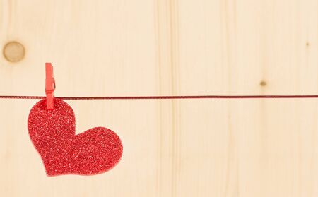 one decorative red hearts hanging on wood background with space for text. photo