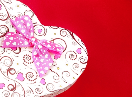 heart gift box: gift box with ribbon on red background with space for text, concept of valentine day