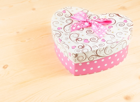 heart shaped stuff: gift box with ribbon on wood table with space for text, concept of valentine day