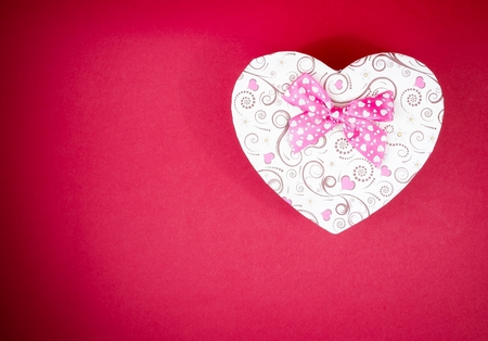 heart shaped stuff: gift box with ribbon on red background with space for text, concept of valentine day