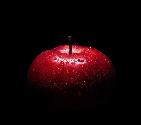 fresh red apple with droplets of water against black with space for text