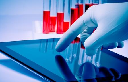 hand i medicinsk blå handske röra modern digital tablett laboratorium. Begreppet medicinsk eller forskningstema Stockfoto