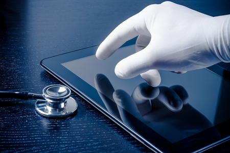 hand in medical glove touching modern digital tablet pc near stethoscope on black wood table. Concept of medical or research theme