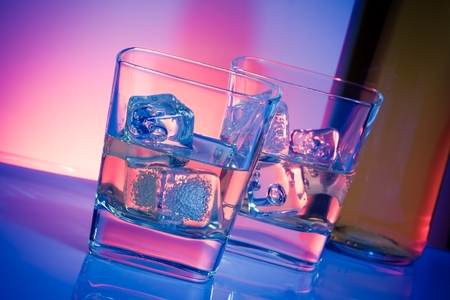 happyhour: a pair of glasses of drink with ice on disco violet light on white table