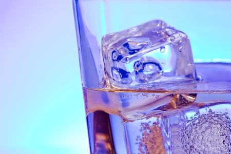 happyhour: glass of alcoholic drink with ice on disco blue light with space for text