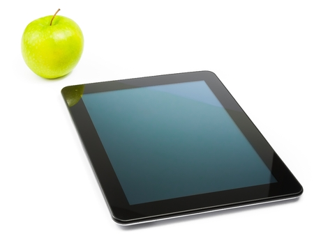 digital tablet pc near green apple on white background photo