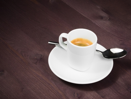 a cup of italian espresso coffee with spoon on old wood table with space for text photo