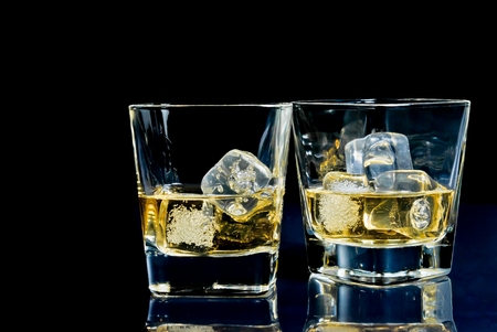 two glasses of alcoholic drink with ice on disco blue light on black table with space for text photo