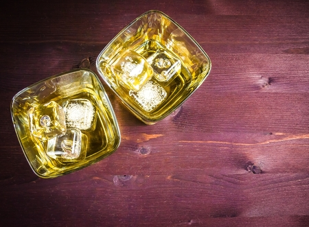 top of view of two glasses of whiskey with ice on old wood table background with space for text Stock Photo
