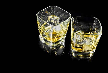 two glasses of alcoholic drink with ice on black background with space for text photo