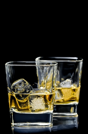 happyhour: two glasses of alcoholic drink with ice on black background with space for text Stock Photo