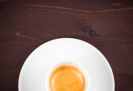 top of view of half cup of italian espresso coffee on old wood table with space for text photo