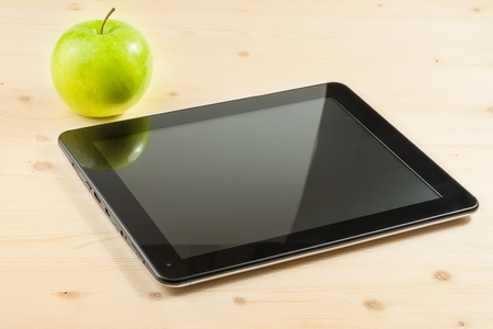 digital tablet pc near green apple on wood table, concept of learn new technology photo