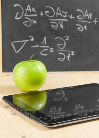 tablet pc and green apple in front of blackboard on wood table, concept of learn new technology photo