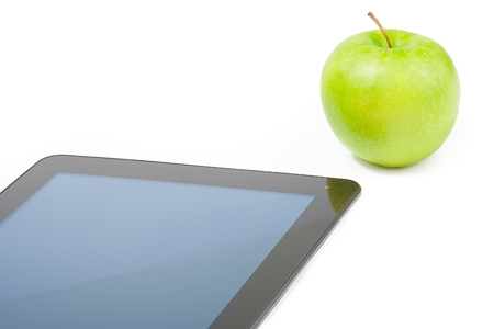 detail of digital tablet pc near green apple on white background, concept of learn new technology photo