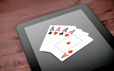poker cards on digital tablet pc on old wood table, concept of  texas poker online photo