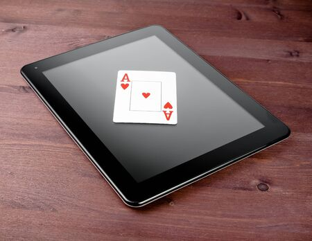 single poker card on digital tablet pc on old wood table, concept of  texas poker online photo
