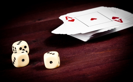 dice near playing card on old wood table, concept of poker game texas  photo