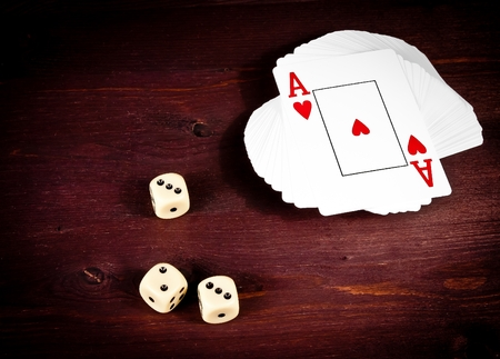 top of view of three dice near playing card on old wood table, concept of poker game texas  photo