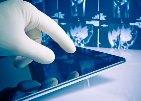 hand in medical blue glove touching modern digital tablet on x-ray images background. Concept of medical or research theme Stock Photo