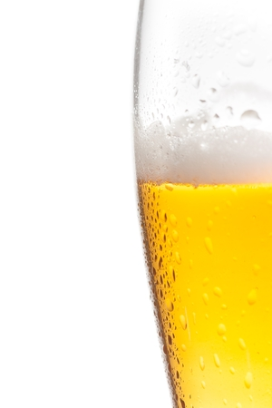 glass half full: half glass of fresh beer with drops on white background, with space for text