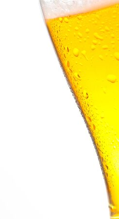 tilted: tilted glass of fresh beer with drops on white background, with space for text